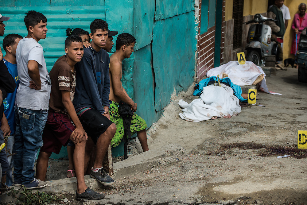 PLAN DE MANZANO, VENEZUELA - NOVEMBER 13, 2016: Bystanders watch as police investigators work a triple homicide crime scene.  A severe economic crisis in Venezuela, caused by the drop in oil prices and years of economic mismanagement under a Socialist government, has lead to an alarming rise in crime and insecurity in the country.  Hyperinflation has left both the working class and professional class of workers with salaries that cannot purchase enough food to feed their families. Many people are turning to crime to make ends meet.  PHOTO: Meridith Kohut for The New York Times