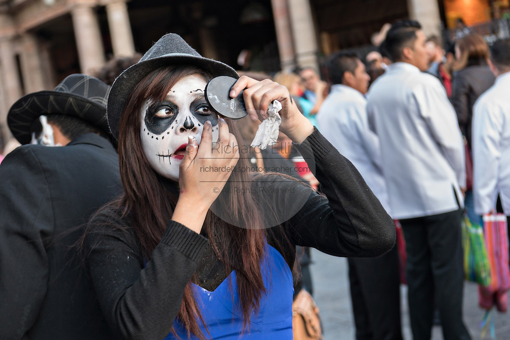 A young woman applies costume make up to to look like a skeleton for the Day of the Dead festival in the Jardin Principal October 28, 2016 in San Miguel de Allende, Guanajuato, Mexico. The week-long celebration is a time when Mexicans welcome the dead back to earth for a visit and celebrate life.