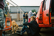 A man and a dog outside at DJ Gordie's 71st birthday party, Hackney Wick, London 2017