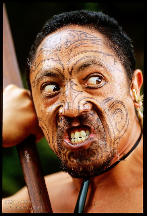 Traditional Maori performer glances to side and grimaces as he performs at Waimangu Volcanic Valley; Rotorua, New Zealand.