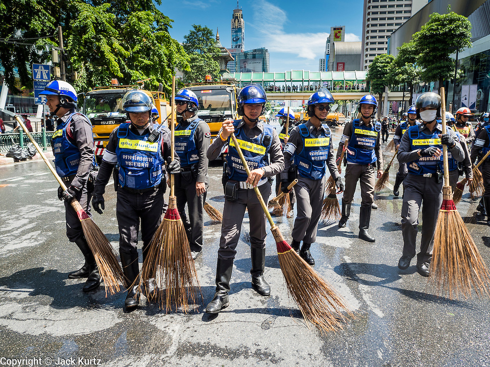 18 AUGUST 2015 - BANGKOK, THAILAND: Thai police clean the street in front of Erawan Shrine Tuesday. The street was covered in debris after a bomb went off in the shrine. An explosion at Erawan Shrine, a popular tourist attraction and important religious shrine in the heart of the Bangkok shopping district, killed at least 20 people and injured more than 120 others, including foreign tourists, during the Monday evening rush hour. Twelve of the dead were killed at the scene. Thai police said an Improvised Explosive Device (IED) was detonated at 18.55. Police said the bomb was made of more than six pounds of explosives stuffed in a pipe and wrapped with white cloth. Its destructive radius was estimated at 100 meters.    PHOTO BY JACK KURTZ