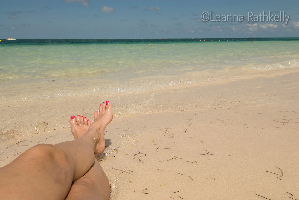Legs relax on the white sand of Bavaro Beach, a popular tourist destination.