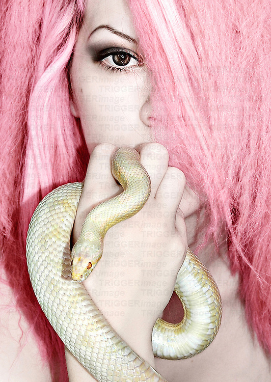 Portrait of a woman with pink hair and an albino snowcorn snake