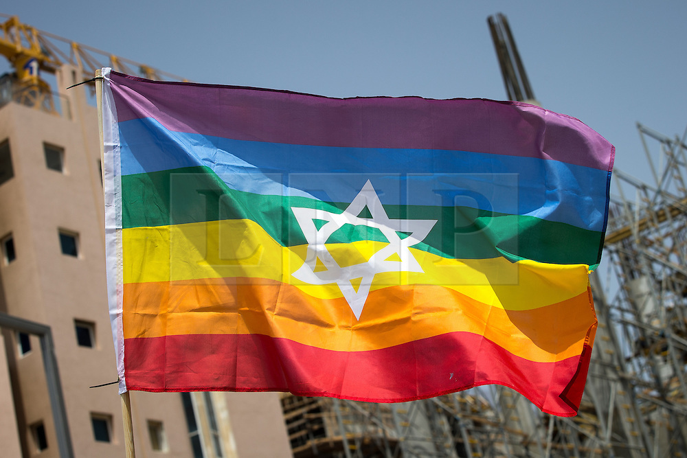"""© Licensed to London News Pictures . 03/06/2016 . Tel Aviv , Israel . A rainbow flag with a Star of David in the centre . Over 100,000 people attend the gay pride parade in Tel Aviv , reported to be the largest such event in the Middle East and Asia . The Israeli government has been accused of using the event as """" pinkwashing """" , marketing the event in order to deflect accusations of poor human rights behaviour . Photo credit: Joel Goodman/LNP"""