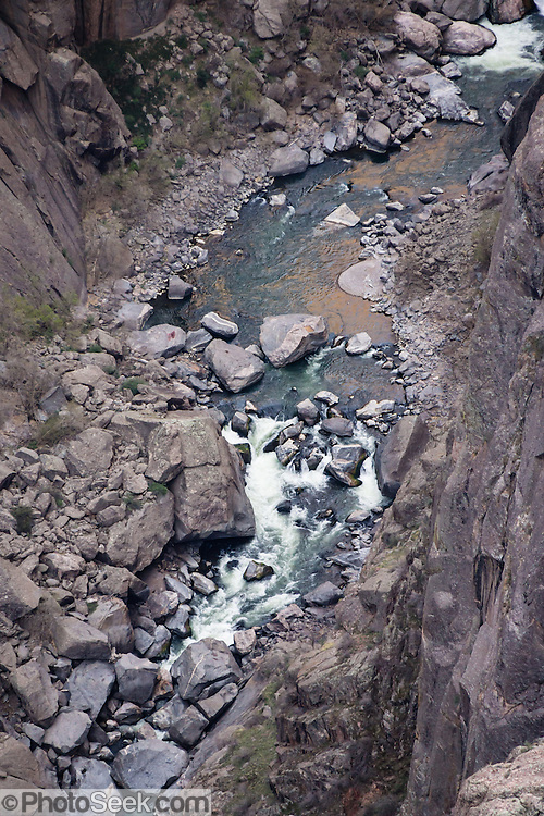 See the Gunnison River far below Devil's Overlook, in Black Canyon of the Gunnison National Park, near Montrose, Colorado, USA. The canyon exposes you to some of the steepest cliffs, oldest rock, and craggiest spires in North America. With two million years to work, the Gunnison River, along with the forces of weathering, has sculpted this vertical wilderness of rock, water, and sky.