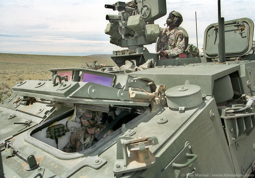Sgt. Joseph Stancil, part of A Company, 5th Battalion, 20th Infantry, checks the weapons system of his Stryker medium weight armored vehicle at the Yakima Training Center in Washington on Thursday June 27, 2002 while his drive waits for orders to move. Alpha Company is the first to receive the $2.5 million Stryker which is the Army's first new armored vehicle in 14 years. It is meant to fill the gap between light infantry that uses only Humvees for transport and heavy armor like the M1 Abrahams tank. ..Able to withstand heavy machine gun rounds but not anti-tank rounds or rocket propelled grenades the Stryker's key assets are rapid transport of its nine man squad overland or by the main in-theater cargo plane, the C-130. The Stryker is also using the FBCB2 computer system allowing each vehicle to know friendly and enemy positions, real-time battlefield intelligence, email, gps mapping, and feeds from remote surveilance aircraft. It is also equiped with a .50 caliber machine gun or grenade launcher with video and thermal imaging operated remotely from within the vehicle...According to Army personel, if the battalion had been ready it would have been one of the first units into Afghanistan. As it is, it will represent the Army's new medium weight brigades in the Millenium Challenge excercises at Ft. Irwin, California, in late July. The live and computer simulated excercise will test the U.S. Military's concept for working together.