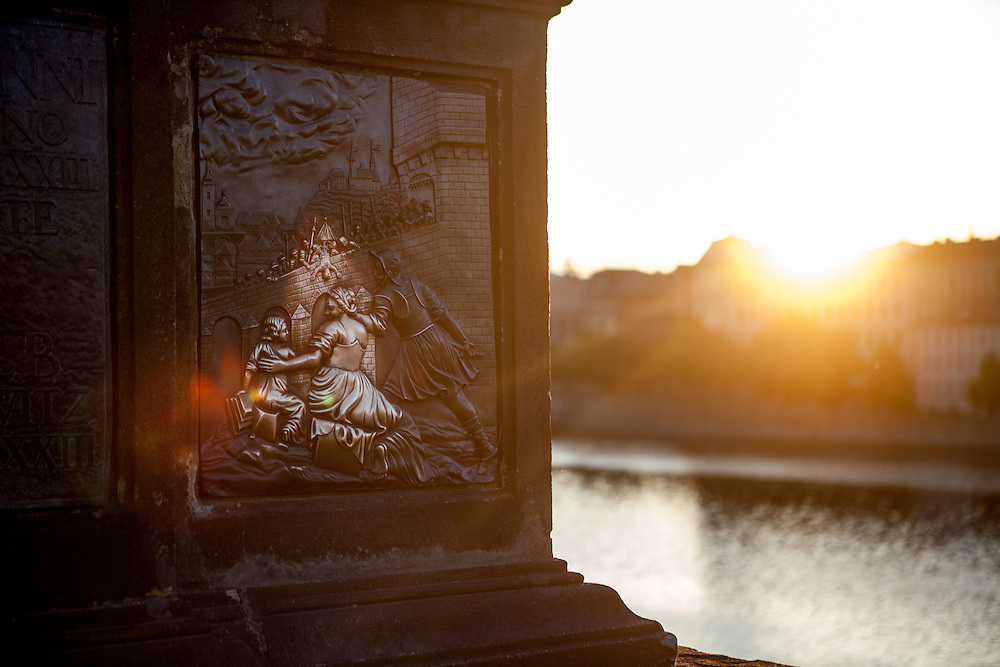 St. John of Nepomuk Statue during sunrise. Touching the statue is a Prague ritual. It is supposed to bring good luck and to ensure that you return to Prague soon.