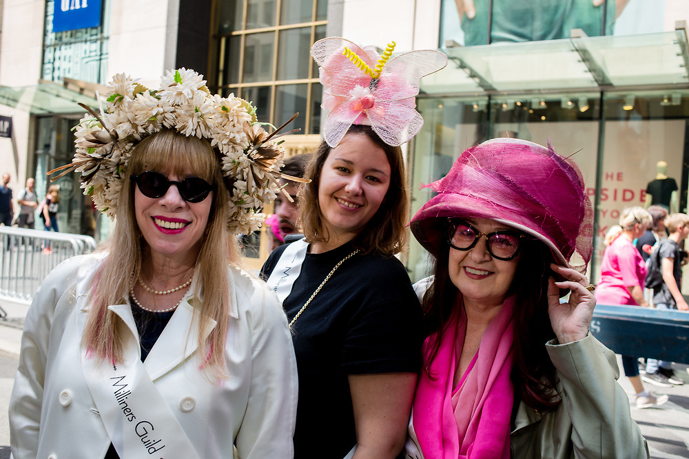 New York, NY - April 16, 2017. Three woman from The Milliners Guid wear hats of their own creation  at New York's annual Easter Bonnet Parade and Festival on Fifth Avenue. From left to right: Linda Ashton, Juliette Chauvin, and Ellen Christine.