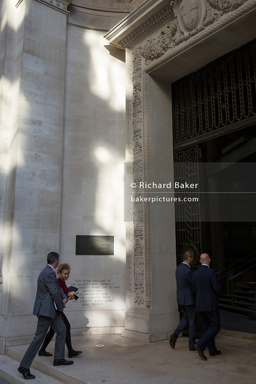 Insurance businessmen enter the former classical entrance to Lloyds of London on Leadenhall Street in the City of London - the capital's financial district, on 10th October 2018, in London, England.