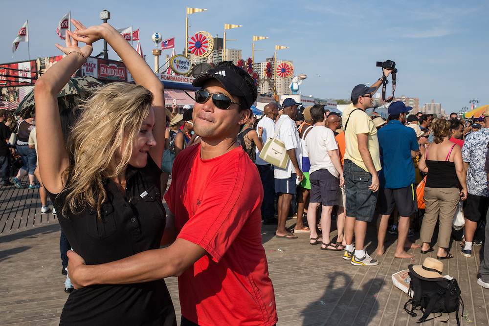 A couple dancing on the Coney Island boardwalk.
