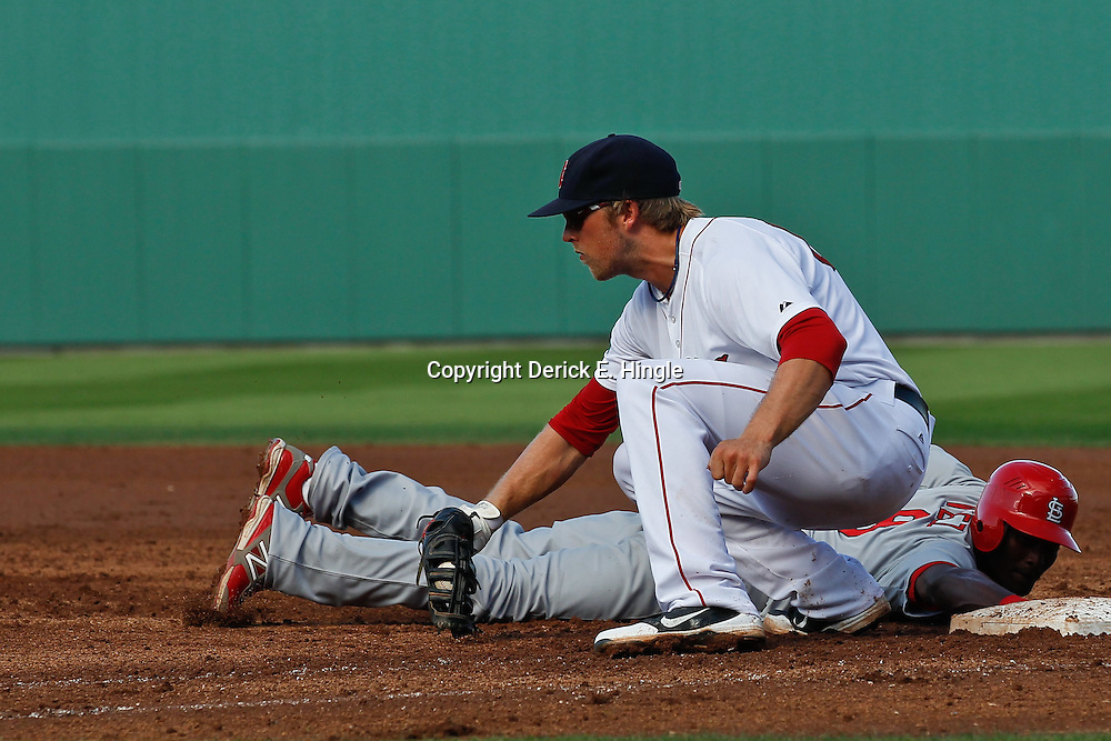 March 15, 2012; Fort Myers, FL, USA; St. Louis Cardinals shortstop Eugenio Velez (8) dives back to the bag before Boston Red Sox first baseman Lars Anderson (62) can make a tag during the top of the eighth inning of a spring training game at Jet Blue Park. Mandatory Credit: Derick E. Hingle-US PRESSWIRE