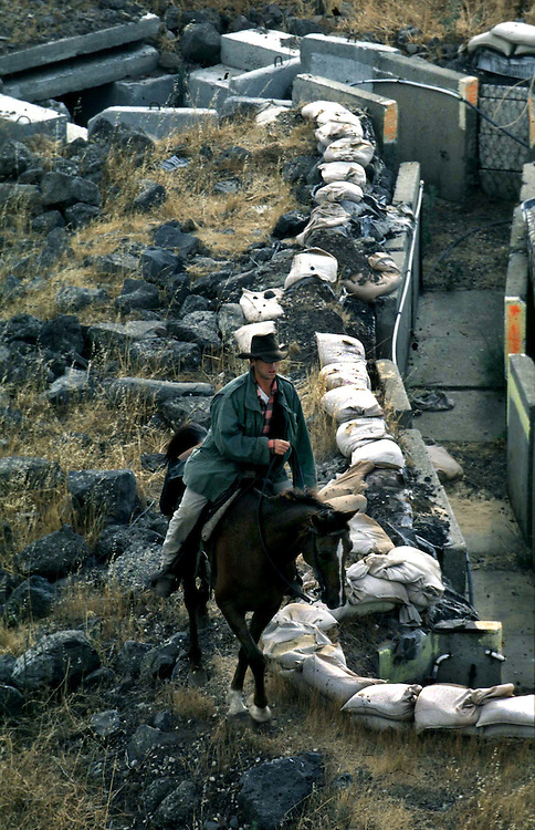 Ofer Hiltovski 30 riding his horse next to a foxhole on the border with Syria during a morning patrols watching the flock of Moshav Yehonatan in the Golan height, Israel. Wednesday October 6 1999....