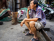 "29 DECEMBER 2018 - BANGKOK, THAILAND: A man takes a smoke break while making longevity noodles in his family shophouse. The family has been making traditional ""mee sua"" noodles, also called ""longevity noodles"" for three generations in their home in central Bangkok. They use a recipe brought to Thailand from China. Longevity noodles are served on special occasions, especially Chinese New Year, which is February 4, 2019.        PHOTO BY JACK KURTZ"