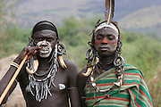 Africa, Ethiopia, Debub Omo Zone, Mursi tribesmen. A nomadic cattle herder ethnic group located in Southern Ethiopia, close to the Sudanese border. A warrior with warthog fangs earring decoration and woman