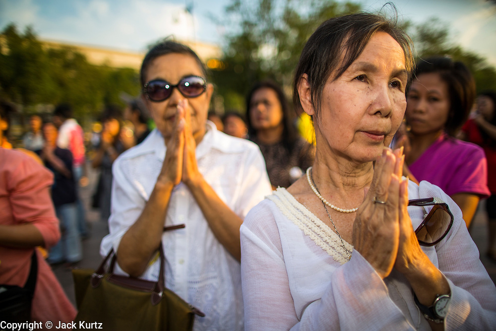 06 JANUARY 2013 - BANGKOK, THAILAND:  Women pray on a sidewalk in Bangkok during a service for a relic of the Buddha's hair. The relic has been on display in Bangkok for about 10 years. There was a ceremony in Sanam Luang in Bangkok Sunday to honor the relic. People prayed for it and received blessings from Buddhist monks and Brahmin priests who presided over the service. The hair is being moved to Ayutthaya, where it will be displayed in a Buddhist temple. The piece of hair has been on loan to Thai Buddhists from a Buddhist temple in Sri Lanka.   PHOTO BY JACK KURTZ