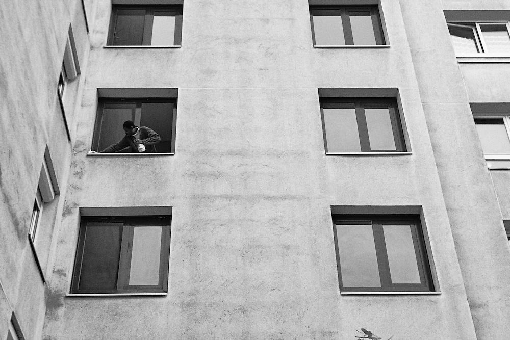 Est parisien. Un homme nettoie une fenêtre donnant sur la voie ferrée, dans le 20ème arrondissement, près de la salle de concert de La Flèche d'Or.