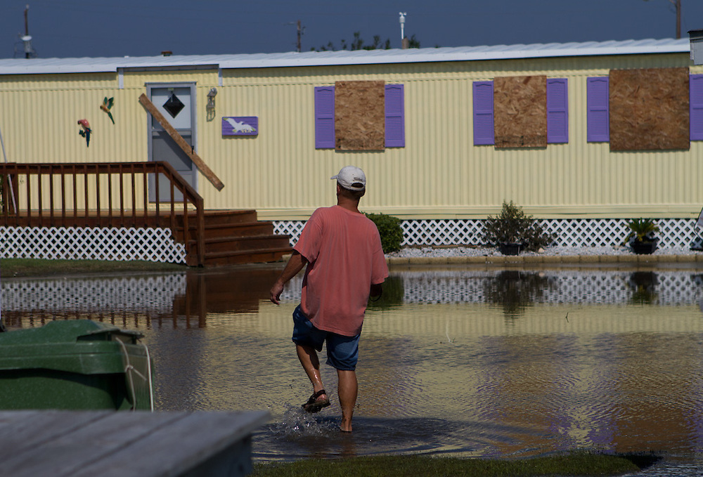 Jack Pierce wades through standing water to survey the damage to mobile homes in Triple S Marina Village, in Atlantic Beach, N.C. One trailer was demolished during the high winds and rain of Hurricane Irene, which made landfall in the area early Saturday morning. Pierce owns a unit that was intact. The majority of the trailers in this park sustained only minor damages, mostly to their roofs and awnings. ..Atlantic Beach was largely spared from the worst of the storm, but residents are likely to remain without power until crews can repair feeds to the area. The bridge to the island was opened upon surveillence of the damage and the beginnings of power restoration.