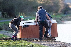 © Licensed to London News Pictures. 29/12/2015. Elland UK. A group of men retrieve a hot tub that has been left stranded on the banks of the Calder & Hebble Navigation at Park Nook Lock in Elland after recent flooding.  Photo credit: Andrew McCaren/LNP