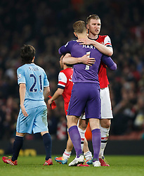Man City Goalkeeper Joe Hart (ENG) hugs Arsenal Defender Per Mertesacker (GER) after the game finishes in a 1-1 draw - Photo mandatory by-line: Rogan Thomson/JMP - 07966 386802 - 29/03/14 - SPORT - FOOTBALL - Emirates Stadium, London - Arsenal v Manchester City - Barclays Premier League.