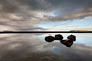 Boulders in sky reflection form small islands in a huge mirror-flat beach pool at Penmaenmawr, Gwynedd, North Wales. The Great Orme at Llandudno is illuminated in sunshine in the distance and the small island of Puffin Island can be seen far left.
