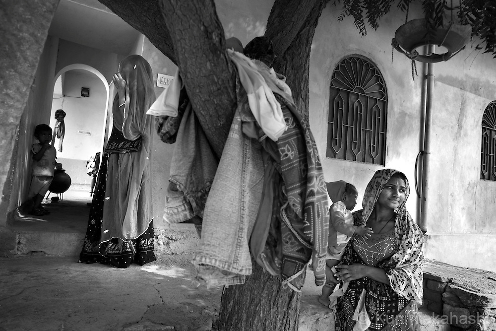 A sex worker holds her baby outside her house in Ingonia, 40km north of Jaipul on Nov 16, 2009. ..
