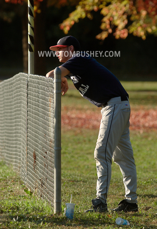 Middletown, NY -  A Dutchess County Community College baseball player watches from behind the outfield fence during a fall baseball game against SUNY Orange in Middletown on Oct. 7, 2007.