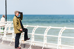 A man looks through binoculars as he stands on Cromer Pier in Norfolk.