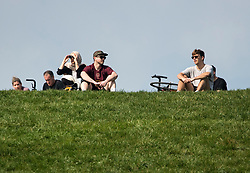 © Licensed to London News Pictures. 12/04/2020. London, UK. People sit in the sun on top of Primrose Hill in London on Easter Sunday, during a pandemic outbreak of the Coronavirus COVID-19 disease. The public have been told they can only leave their homes when absolutely essential, in an attempt to fight the spread of coronavirus COVID-19 disease. Photo credit: Ben Cawthra/LNP