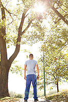 Full length rear view of fit man standing on path in park