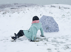 © Licensed to London News Pictures. 10/12/2017. Aberystwyth, UK. A woman falls over while enjoying the first snow of the winter at Aberystwyth on the Welsh coast, as the wintry conditions spread of much of the middle of the UK.  People are out  walking on Constitution Hill overlooking the town, making the most of the snowy scenes .Photo credit: Keith Morris/LNP