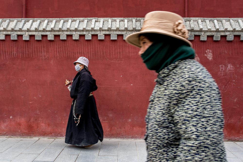 Women walk around the Gyanak mani wall in Yushu prefecture, Tibet (Qinghai, China).