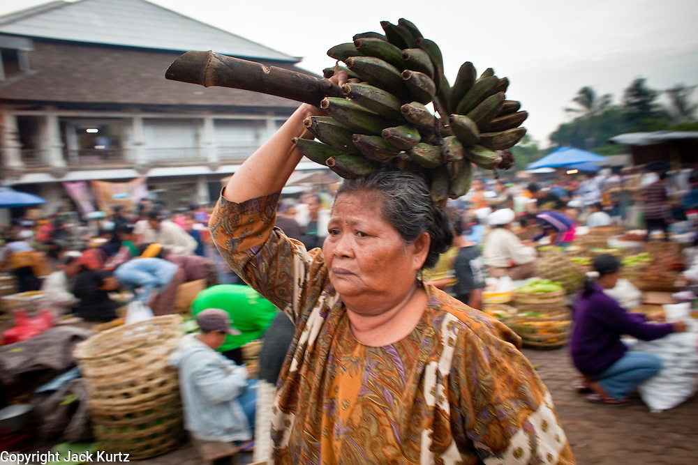 25 APRIL 2010 - PAYANGAN, BALI, INDONESIA: A woman carries plantains on her head in the market in Payangan, Bali. Many Indonesians shop every day because they don't have refrigerators in their homes.  PHOTO BY JACK KURTZ