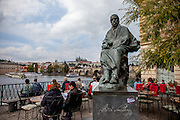 Bedrich Smetana statue beside the museum located close to the Moldau/Vlatava river. In the back Charles Bridge and Prague Castle.