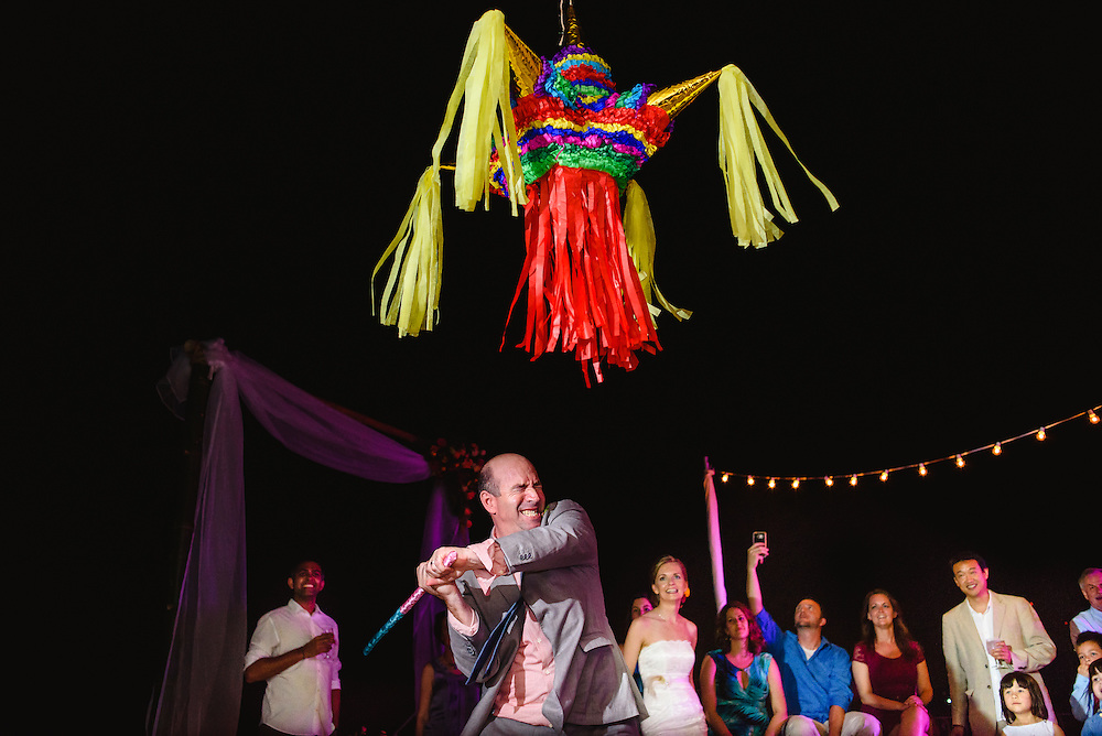 Kathy enjoys watching Mariano trying hard to hit the piñata during their reception in Cinchas Chinas, Puerto Vallarta. Photo by: Melissa Suneson.