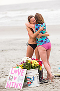 Charleston area surfers embrace as they gather for a traditional memorial paddle out to honor and remember the nine people killed at the historic mother Emanuel African Methodist Episcopal Church June 27, 2015 in Folly Beach, South Carolina. Earlier in the week a white supremacist gunman killed 9 members at the historically black church.