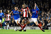 James Ward-Prowse (16) of Southampton is fouled by Oliver Hawkins (9) of Portsmouth and Ben Close (33) of Portsmouth during the EFL Cup match between Portsmouth and Southampton at Fratton Park, Portsmouth, England on 24 September 2019.