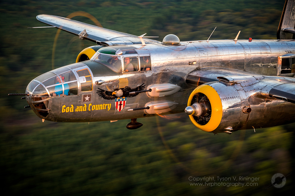 North American B-25J Mitchell bomber, &quot;God and Country&quot;<br /> <br /> God And Country  is a &ldquo;J&rdquo; Model North American B-25 Mitchell, and was built in 1944 at North American's Kansas City plant and was accepted for service in the AAF in early 1945 which was too late to see combat.  She came out of storage in 1946,  and beginning in 1949, served as VIP transport in the new US Air Force until 1958 when she experienced a gear-up landing and was declared as salvage. <br /> <br /> She was bought in 1962 by Tallmantz Aviation of Long Beach, CA and began the next chapter of her life as a photo ship for Hollywood.  Pacific Prowler has participated in over 80 Hollywood feature films including:<br />   Catch 22 <br />   Around The World in 80 Days <br />   For Whom The Bell Tolls <br />   Disney's 360 Degree 'Circle Vision' movies<br /> <br /> In the 1960s, this plane flew to all four corners of the world to film the Seven Wonders Of The World at low level for Disney Studios for use in their 360 degree videos as seen at the Disney Parks.  In the mid-1980s she was sold to Universal Aviation and was operated by Aces High in the UK (as 'Dolly') - being employed specifically to film The Memphis Belle in 1989.  She retired from movie-work in the mid-1990s and went into a serious restoration period.  In 1996, while owned by World Jet of Florida, her camera nose was removed and the traditional military nose replaced From 1996 to 1999 she only flew 60 hours, mostly to air shows as &quot;Girls Rule&quot;.   By the early 2000s she was renamed &quot;Top Secret&quot;, and under the operation of 99th Street Inc. of San Antonio, TX, she hardly flew at all; rather, she languished in disrepair in a falling down hangar.  In late 2002/early 2003, Jim Terry purchased the aircraft and renamed her &quot;Pacific Prowler&quot;. The plane spent the first several months in Tulsa OK, where students at the Tulsa Tech Center and volunteers got the plane airworthy.  For the next 10 yea