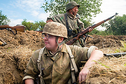 A Reenactor portraying a German Fallschirmjäger or paratrooper from the eastern front fights alongside reenactors depicting Panzer Grenadier Division Großdeutschland soldiers in a small scale skirmish at Ackworth Steam Rally