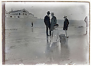 glass plate early 1900s with family on beach near hotel