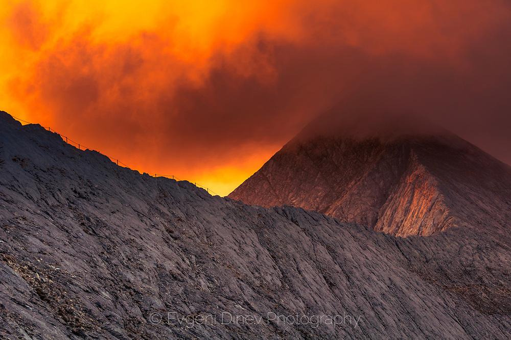 Massive marble peak under red clouds
