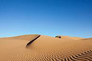 Sahara desert sand dunes with clear blue sky at Erg Lihoudi, M'hamid, Morocco.