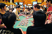 Gamblers play on Roulette tables in a casino, in Singapore, on March 13, 2010. Photo by Juha-Pekka Kervinen/Pictobank
