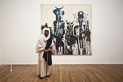 """Sudanese artist Ibrahim El-Salahi, one of the most significant figures in African and Arab Modernism, poses for a picture next to his painting entitled """"Reborn Sounds of Childhood Dreams I (1961-5)"""" at Tate Modern<br /> Monday, 1st July 2013<br /> Picture by Piero Cruciatti / i-Images"""