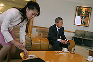 An employee brings cups of tea to the table whilst Takeo Fukui, President and CEO of Honda Motor Co.,Ltd., conducts a meeting, Tokyo, Japan, on Tuesday Nov. 30th 2004.  During interviews it is common for female assistants to enter the rooms silently , bringing refreshment drinks of green tea, coffee, or orange juice, to the company head and his guests.