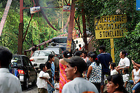 Cars and people line up to cross a bridge over a river. Traffic was stymied here for weeks until road crews could construct a makeshift road in place of one that was washed out when the swollen river overran its banks and altered this area's landscape in early October. Torrential rains associated with Hurricane Stan inundated parts of Central America in early October, causing flooding, mudslides and death across western Guatemala. Many areas have been cut off due to washed out roads and bridges.<br />