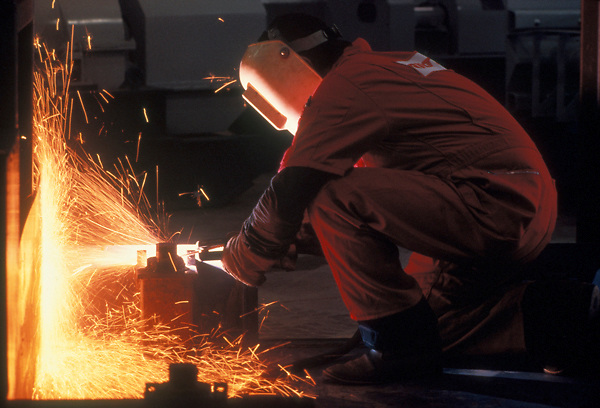 Stock photo of a kneeling man metal grinding and throwing sparks from his tools