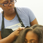 Michelle Munn styles the hair of Liana Slade, 13, at Munn's B Shoppe in Leland, N.C.