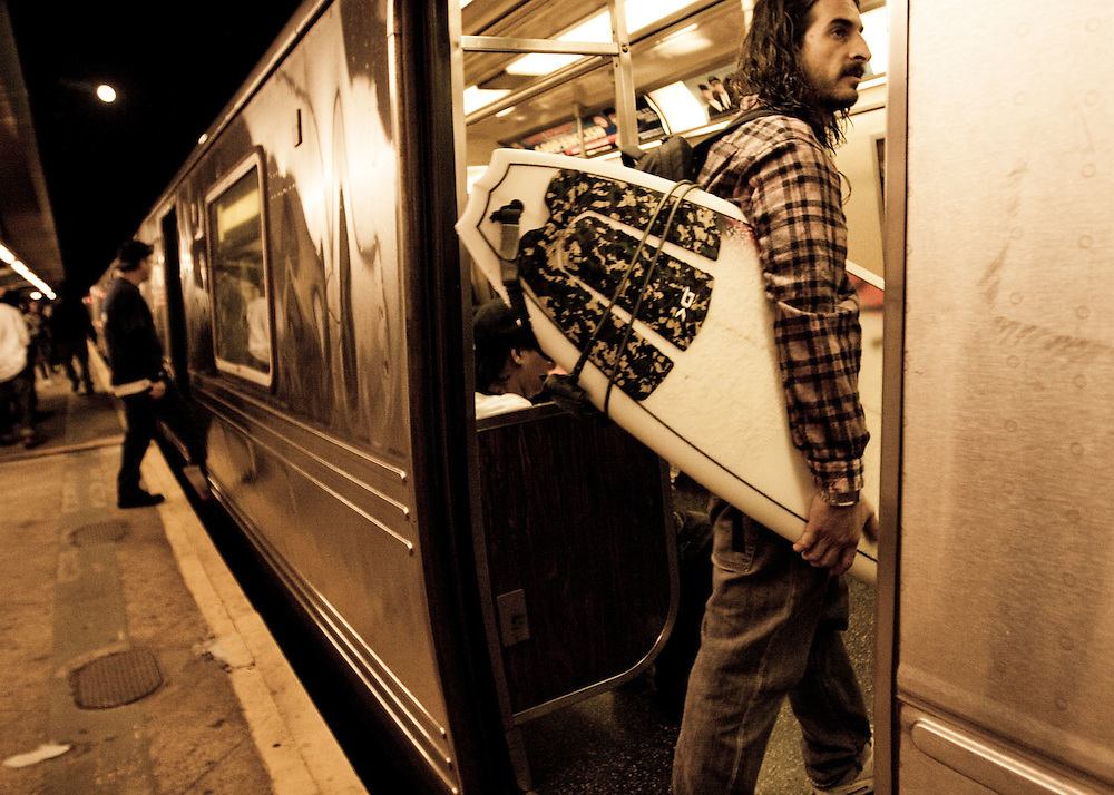A surfer takes the subway back into Manhattan after surfing at Rockaway Beach, Queens, NY.