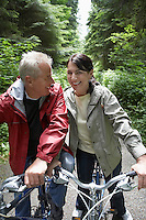 Senior man and middle-aged woman on bikes in forest laughing