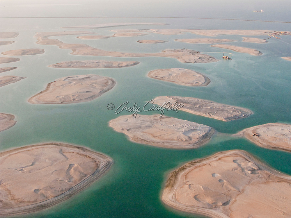 "Aerial view of a dredges forming islands with reclaimed sand. This group of islands is part of ""The World"" a man-made archipelago of 300 islands in the shape of a world map. Located off the cosat of Dubai in the Persian Gulf it will eventually feature entrainment, commercial and residentail properties. Dubai, United Arab Emirates (UAE)"